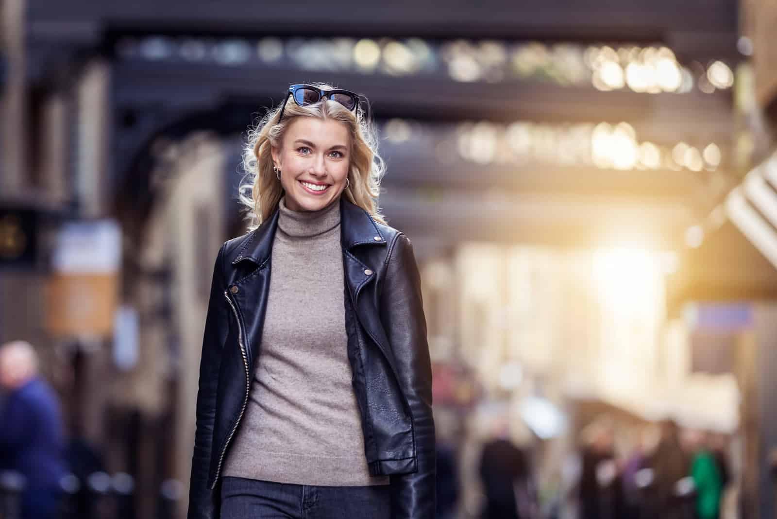 une belle femme aux cheveux blonds marche dans la rue