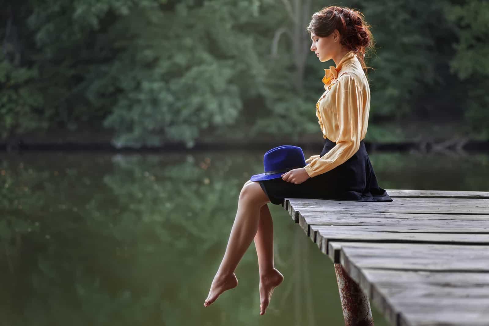une belle femme vêtue d'une robe est assise sur la jetée