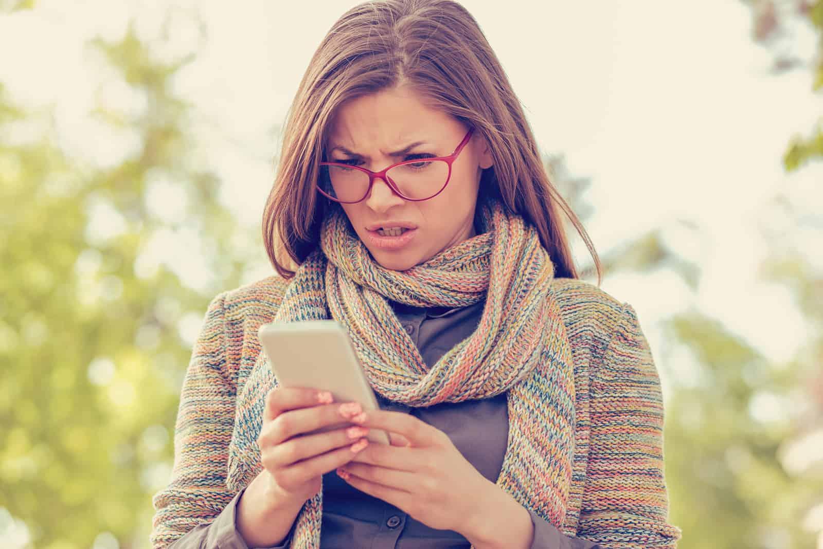 une femme agacée se lève et tient un téléphone dans sa main