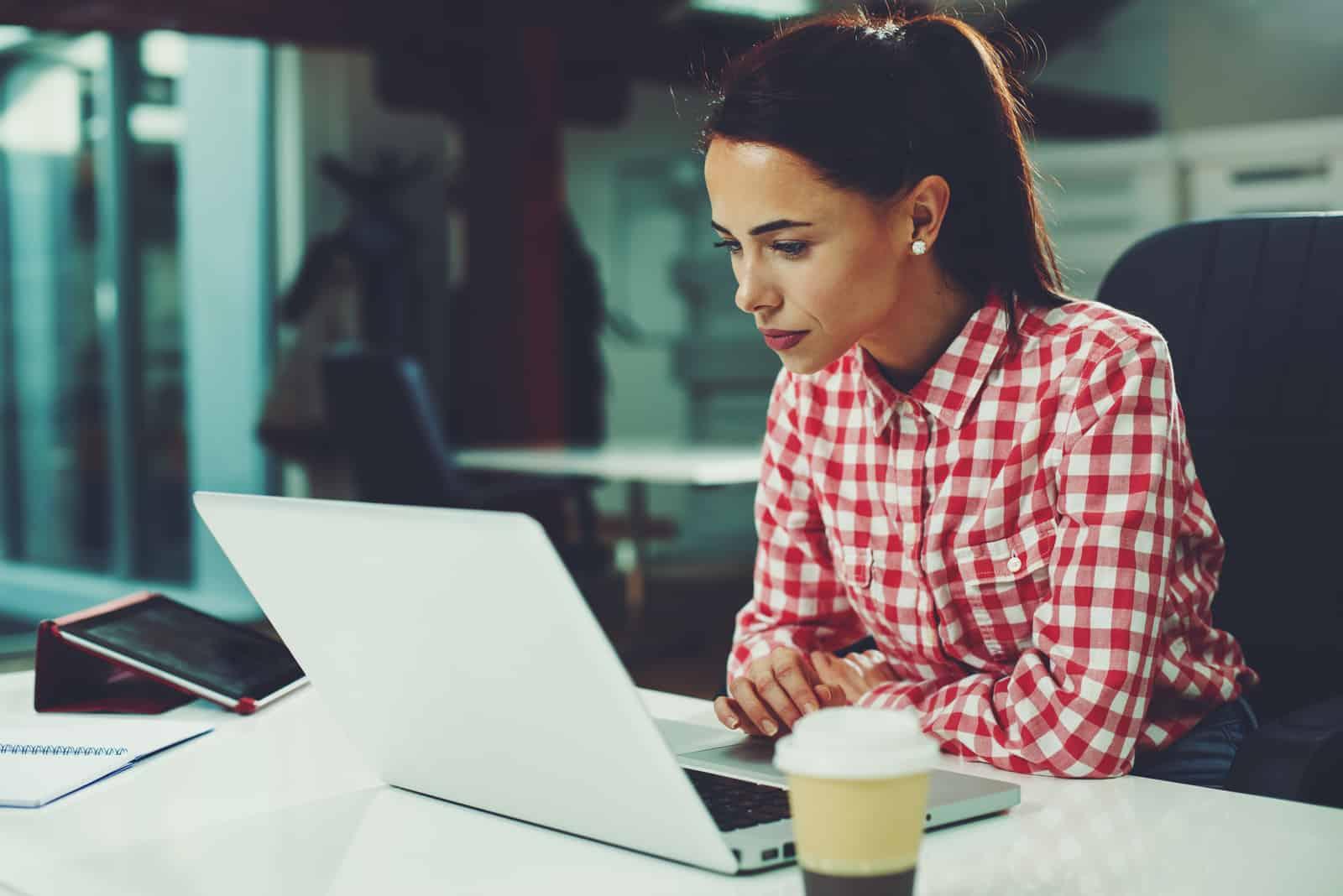 une femme aux cheveux attachés assise derrière un ordinateur portable