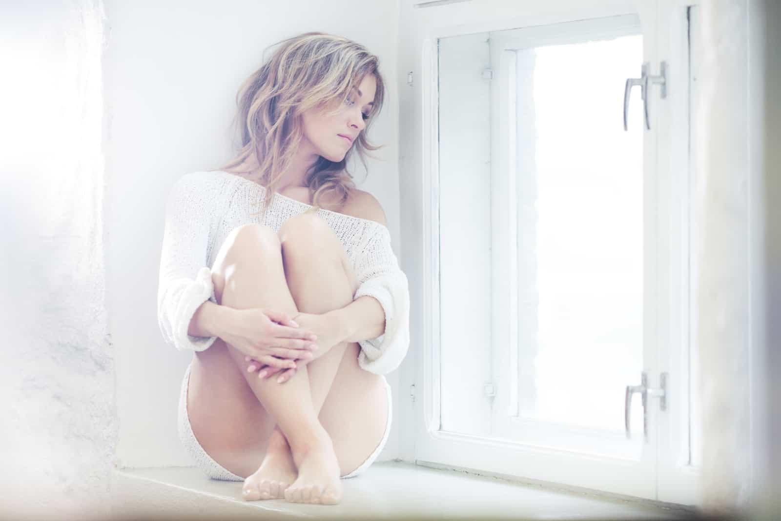 une femme aux cheveux blonds assise près de la fenêtre