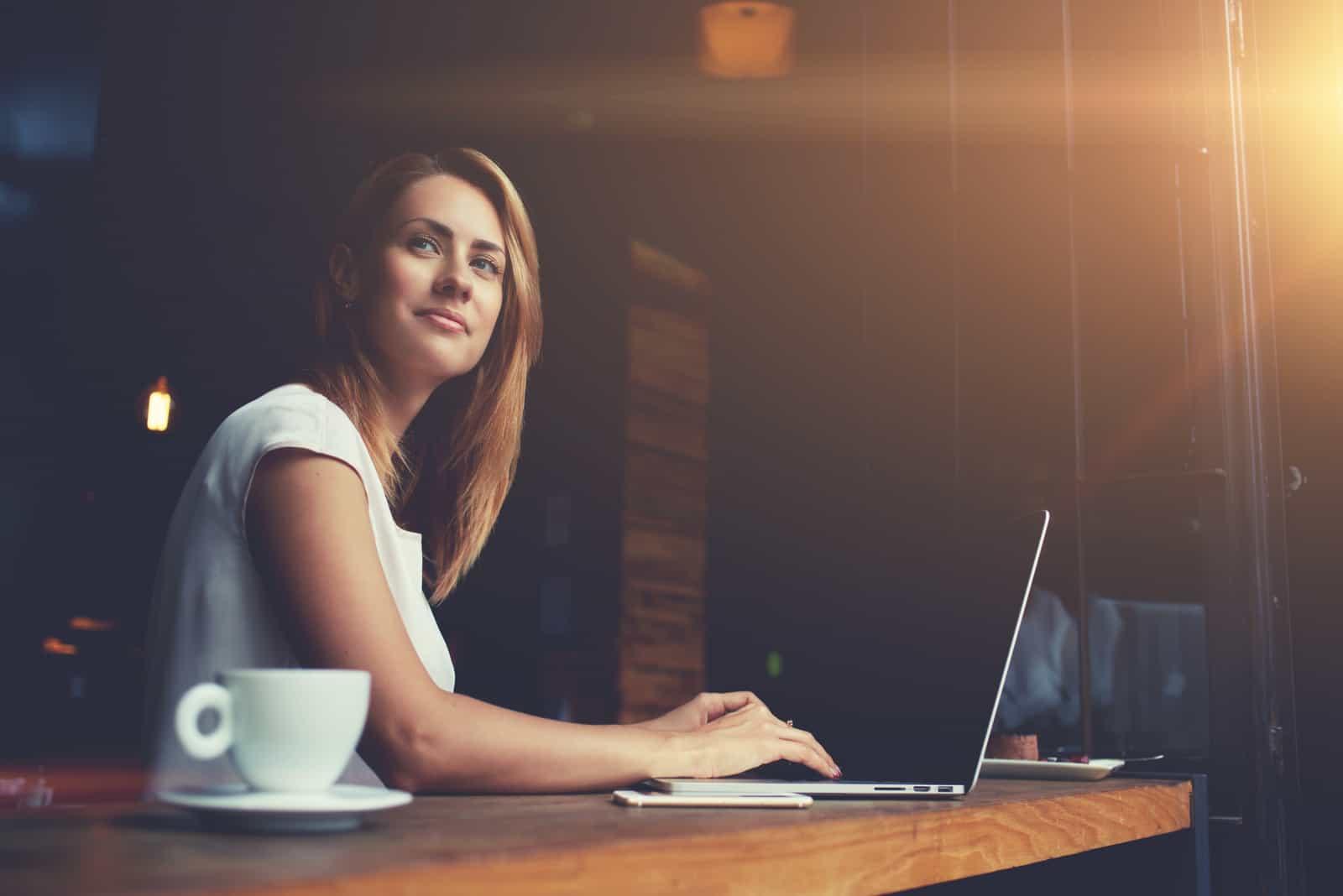 une femme aux cheveux bruns est assise devant un ordinateur portable et boit du café