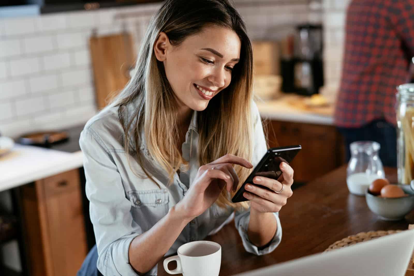 une femme aux cheveux bruns souriante est assise à une table, tenant un téléphone à la main
