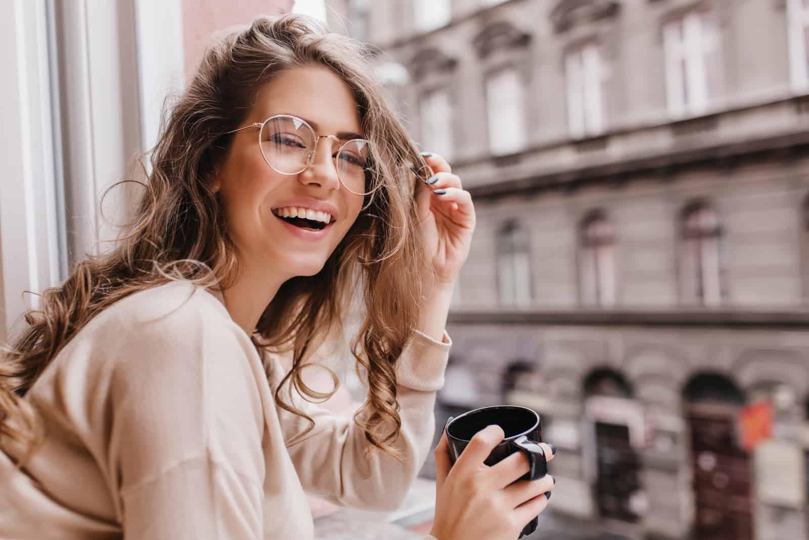 une femme aux cheveux bruns souriante se tient à la fenêtre et boit du café