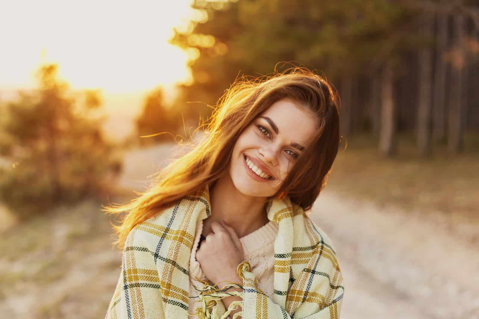 une femme aux cheveux bruns souriante se tient debout