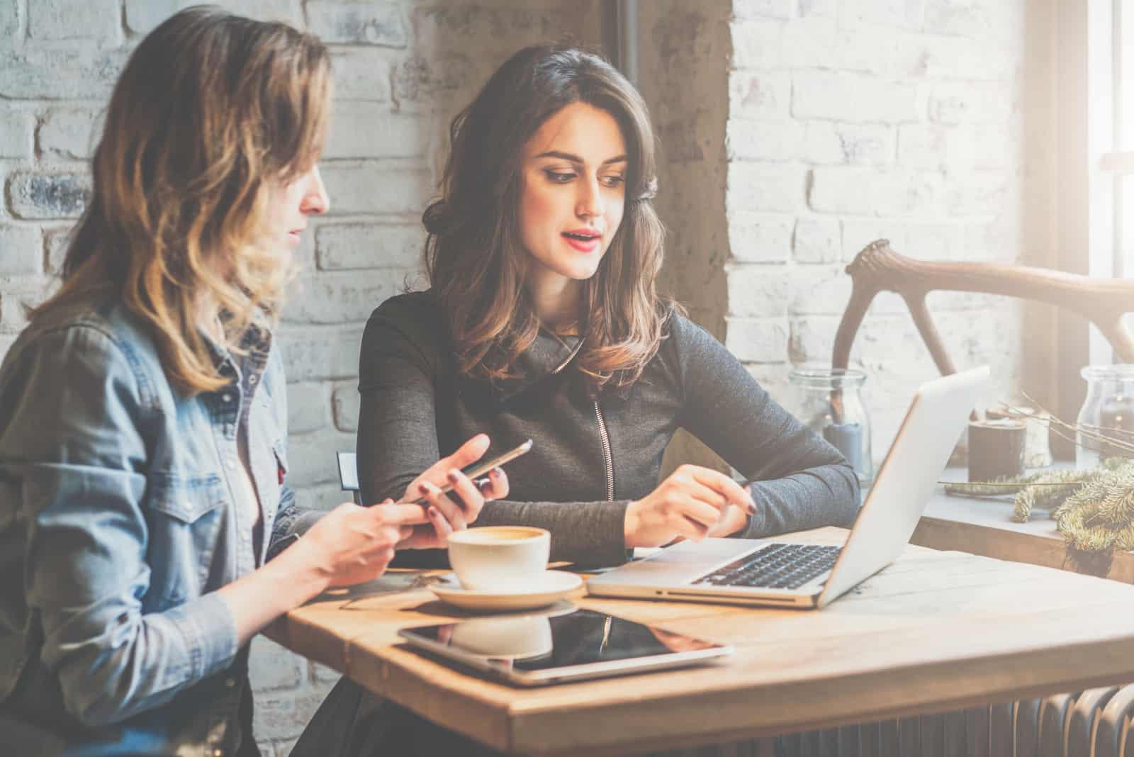 une femme aux cheveux noirs est assise devant un ordinateur portable et parle à un ami