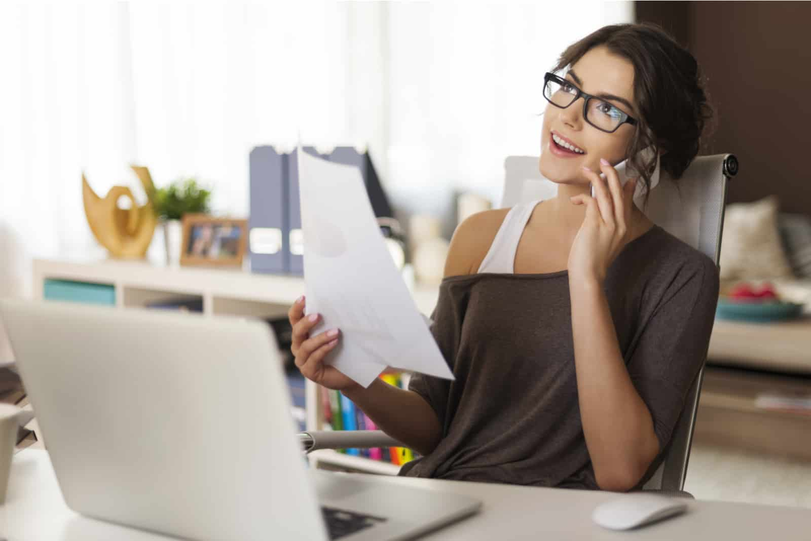 une femme aux cheveux noirs parlant au téléphone alors qu'elle était assise à une table