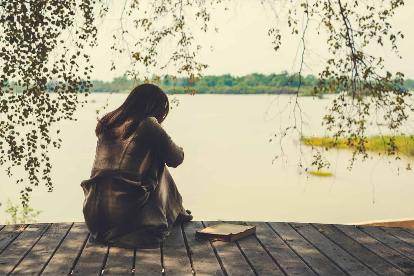 une femme avec un livre à côté d'elle est assise sur la jetée