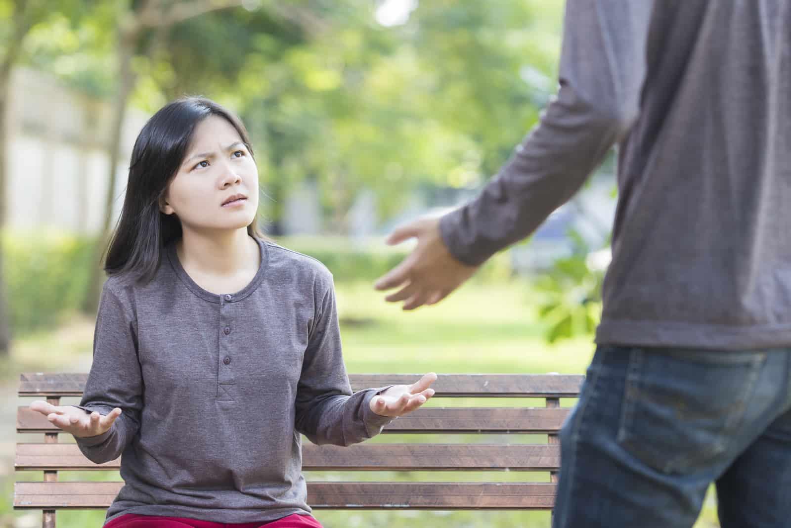 une femme en colère regarde les hommes parler