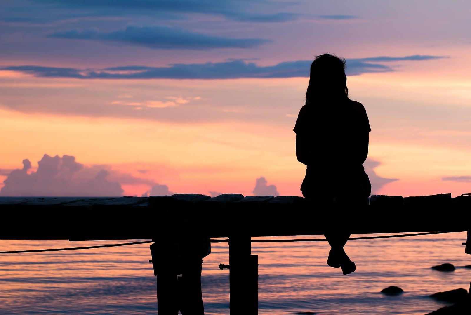 une femme est assise sur un pont en bois et regarde devant elle