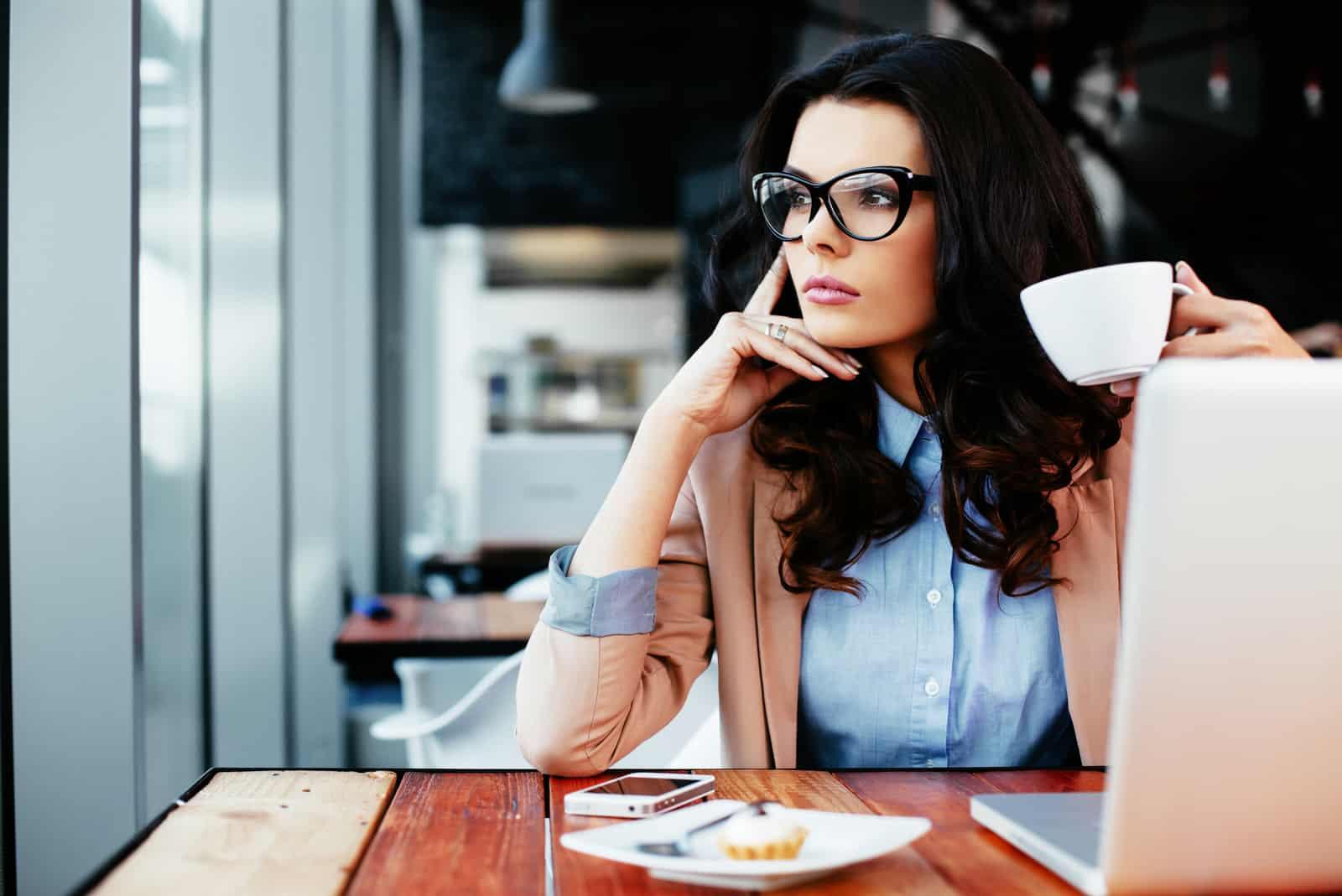 une femme imaginaire est assise à une table et boit du café