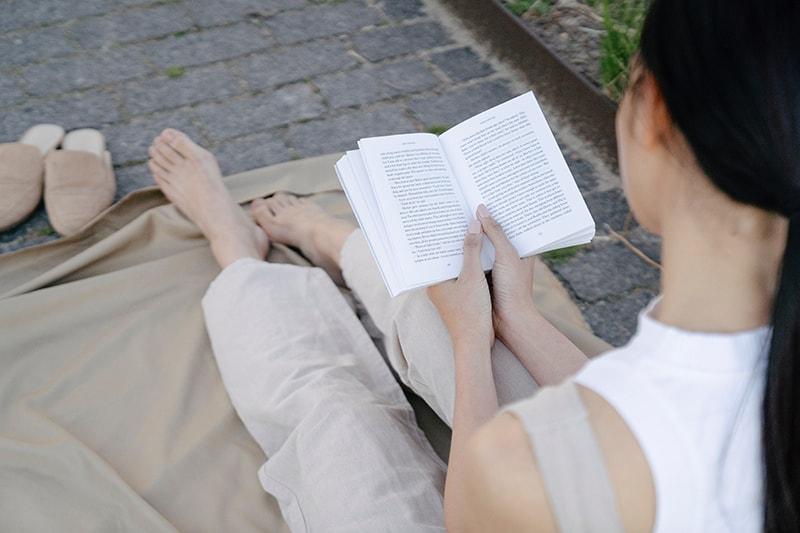 une femme lisant le livre assis dehors sur un tapis marron