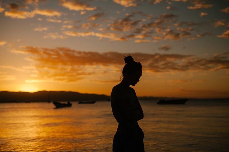 une femme marchant sur la plage au coucher du soleil