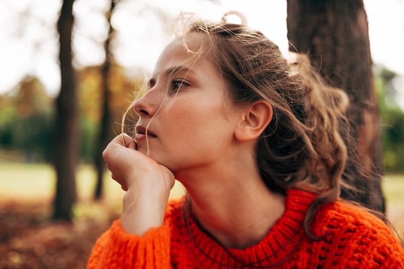 une femme pensive penchant le menton sur la main assis dans le parc