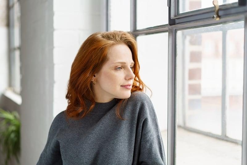 une femme réfléchie positive regardant par la fenêtre