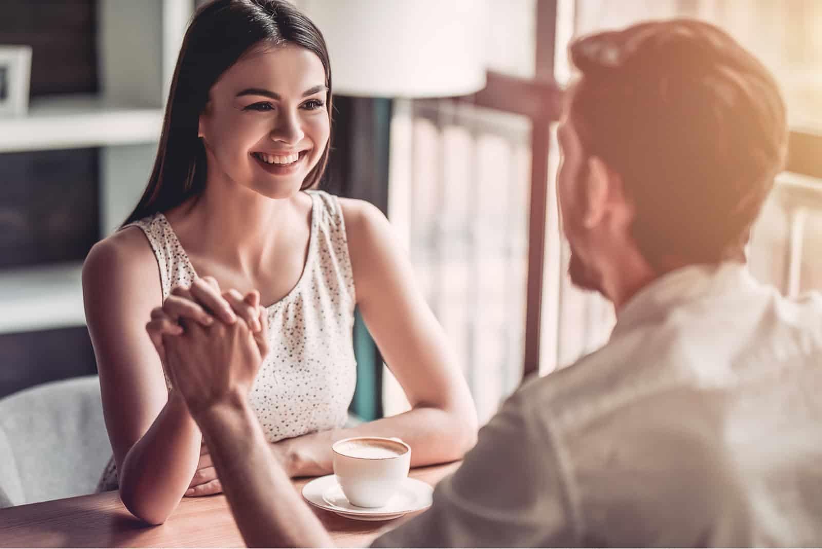 une femme souriante assise à une table avec un homme se tenant la main et parlant