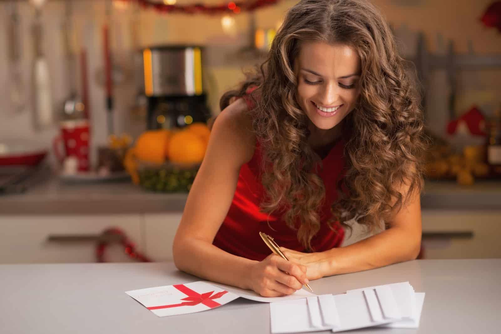 une femme souriante aux cheveux crépus se tient à table et écrit une carte de voeux