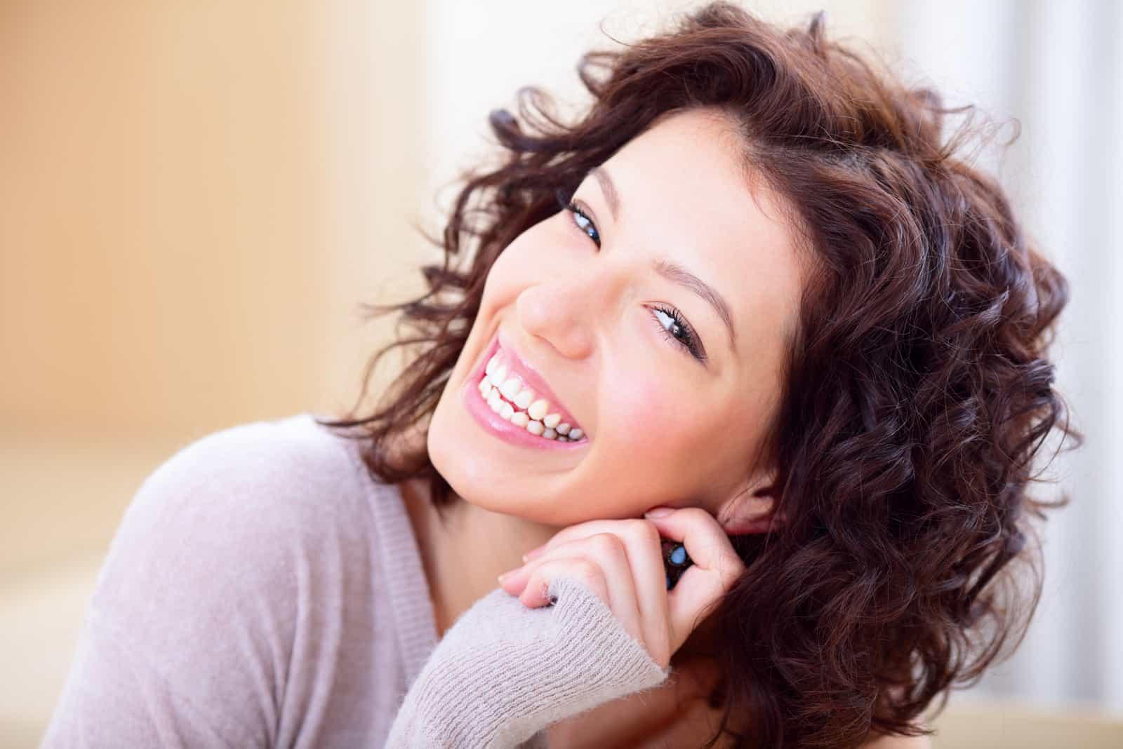 une femme souriante aux cheveux noirs crépus