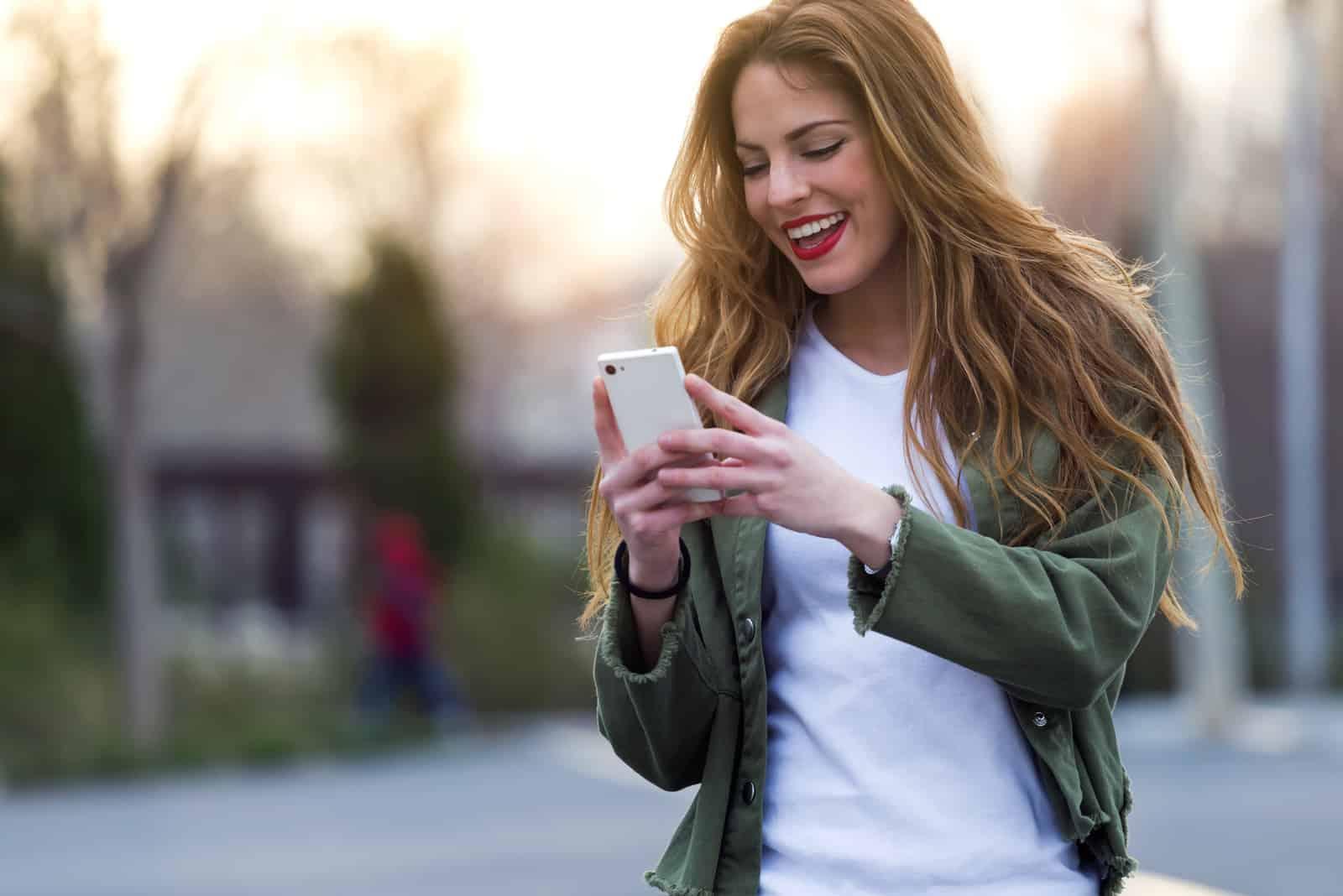 une femme souriante aux longs cheveux bruns se tient dans la rue tenant un téléphone à la main