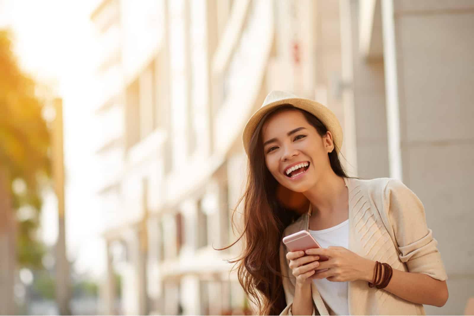 une femme souriante avec un chapeau sur la tête se tient dans la rue et un bouton sur le téléphone
