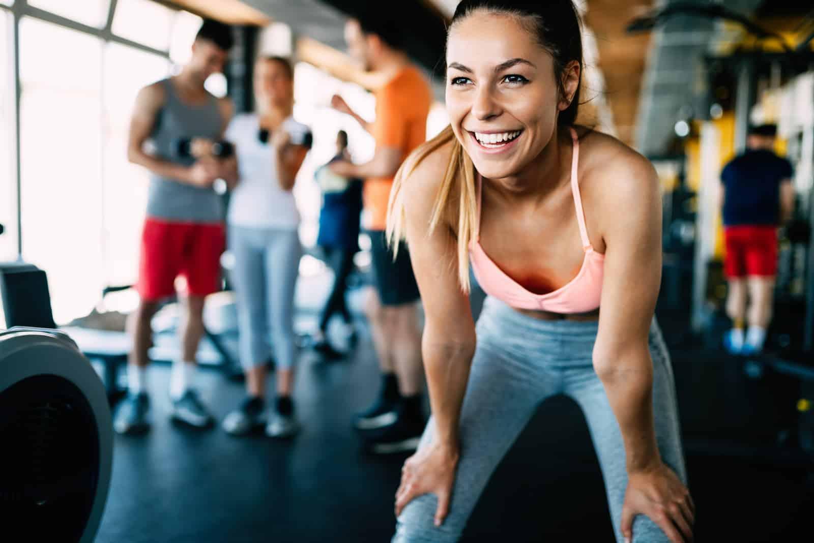 une femme souriante debout dans la salle de gym