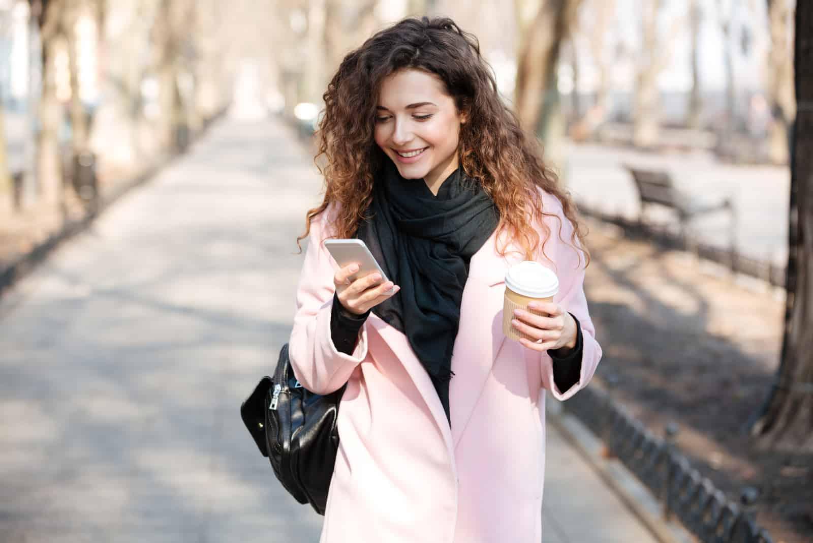 une femme souriante marche dans la rue tenant une tasse de café à la main et un téléphone