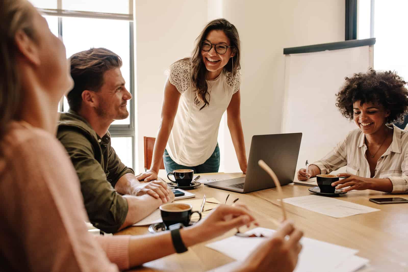 une femme souriante parlant à des collègues