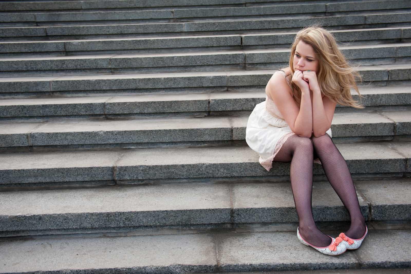 une femme triste assise dans les escaliers