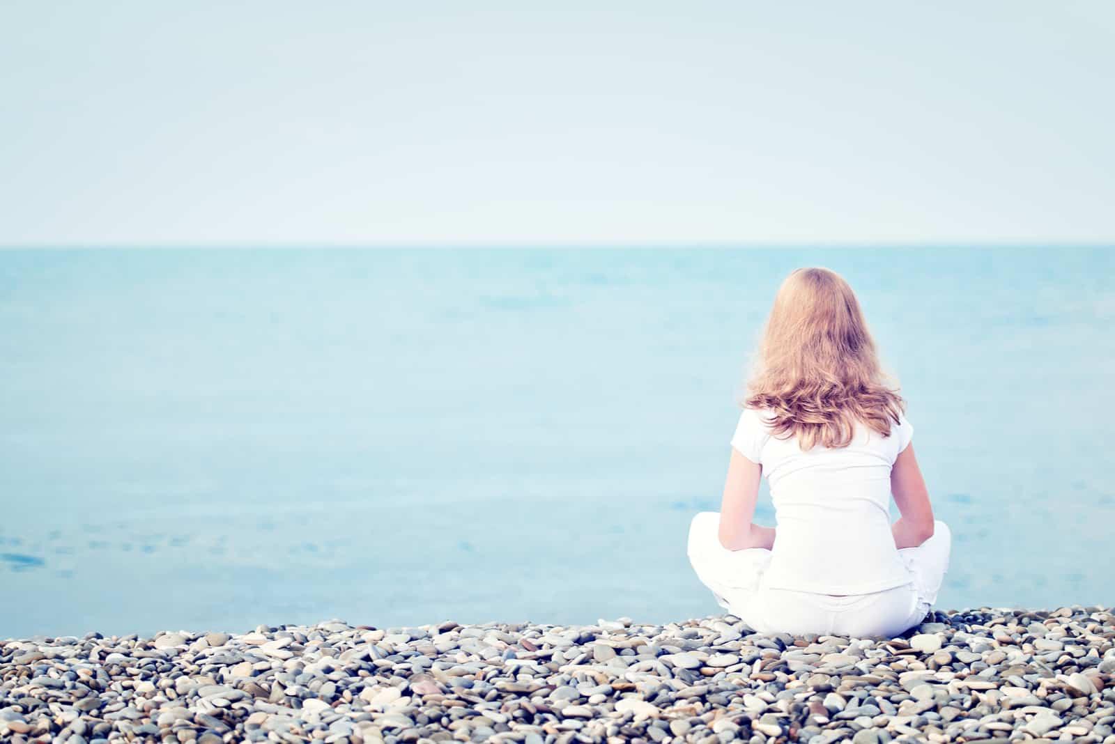 une femme triste assise sur la plage au bord de la mer
