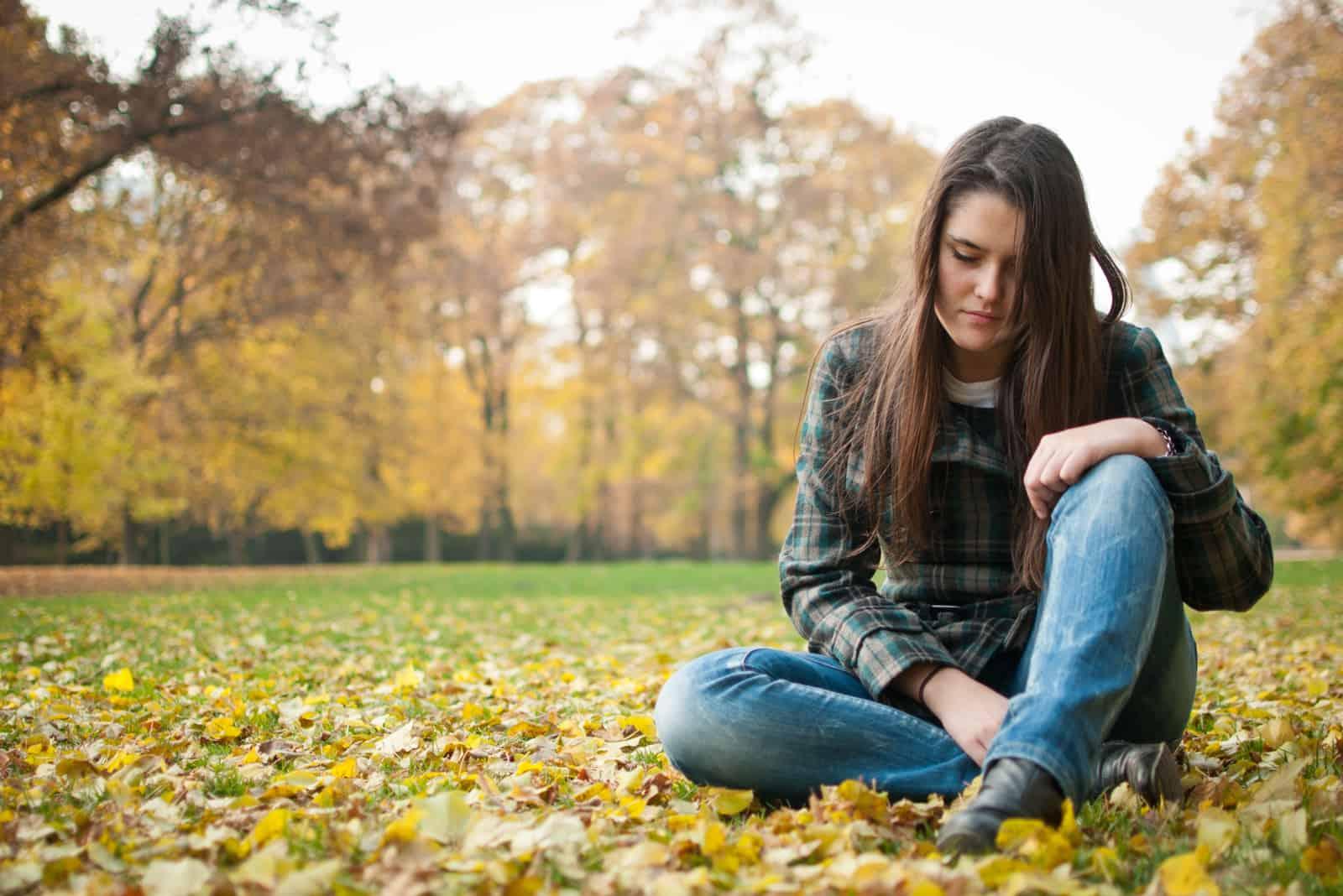 une femme triste assise sur l'herbe