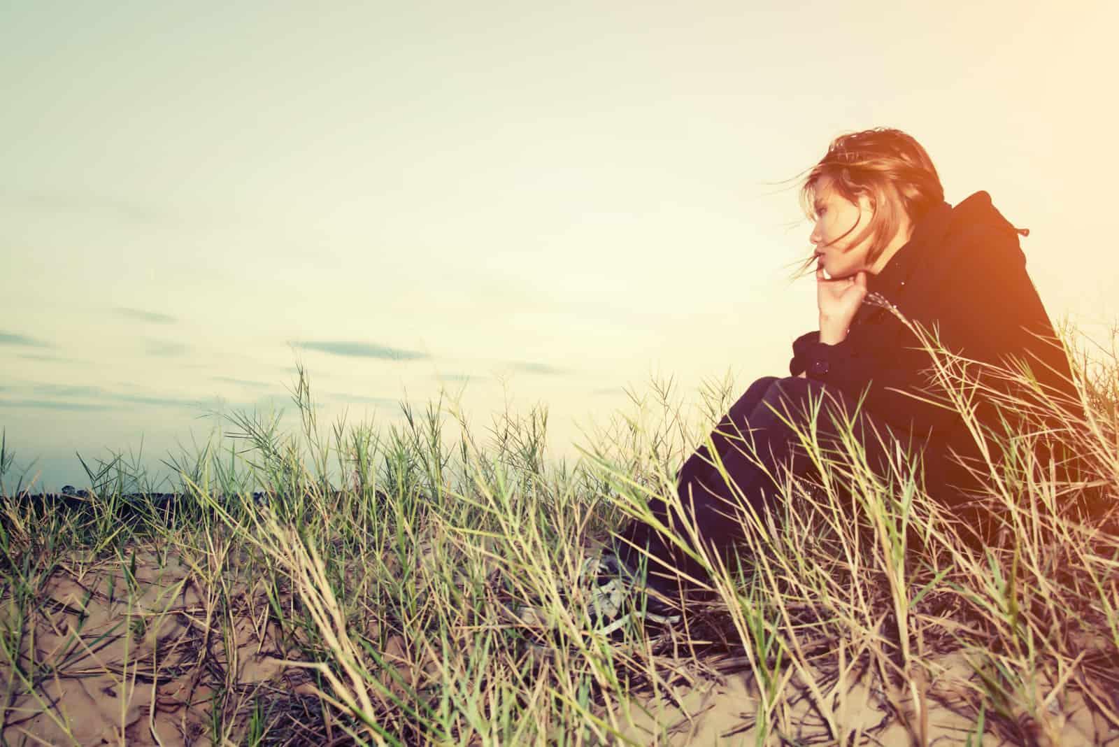 une femme triste est assise sur l'herbe et regarde devant elle