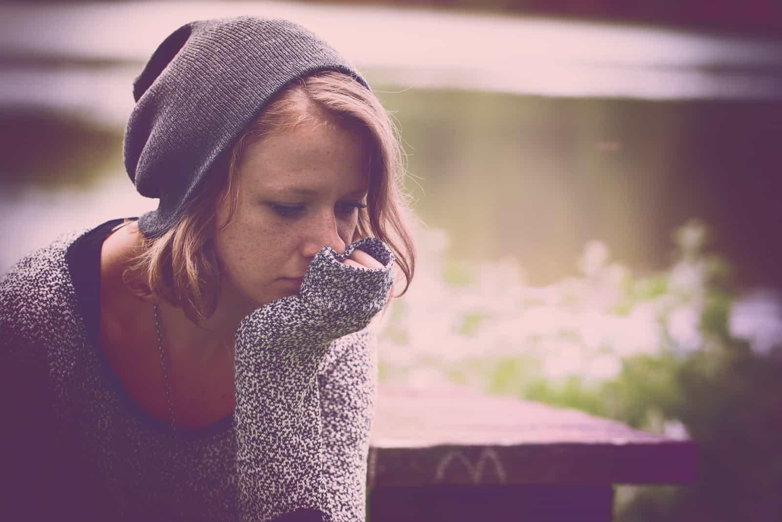 une femme triste est assise sur un banc avec un chapeau sur la tête