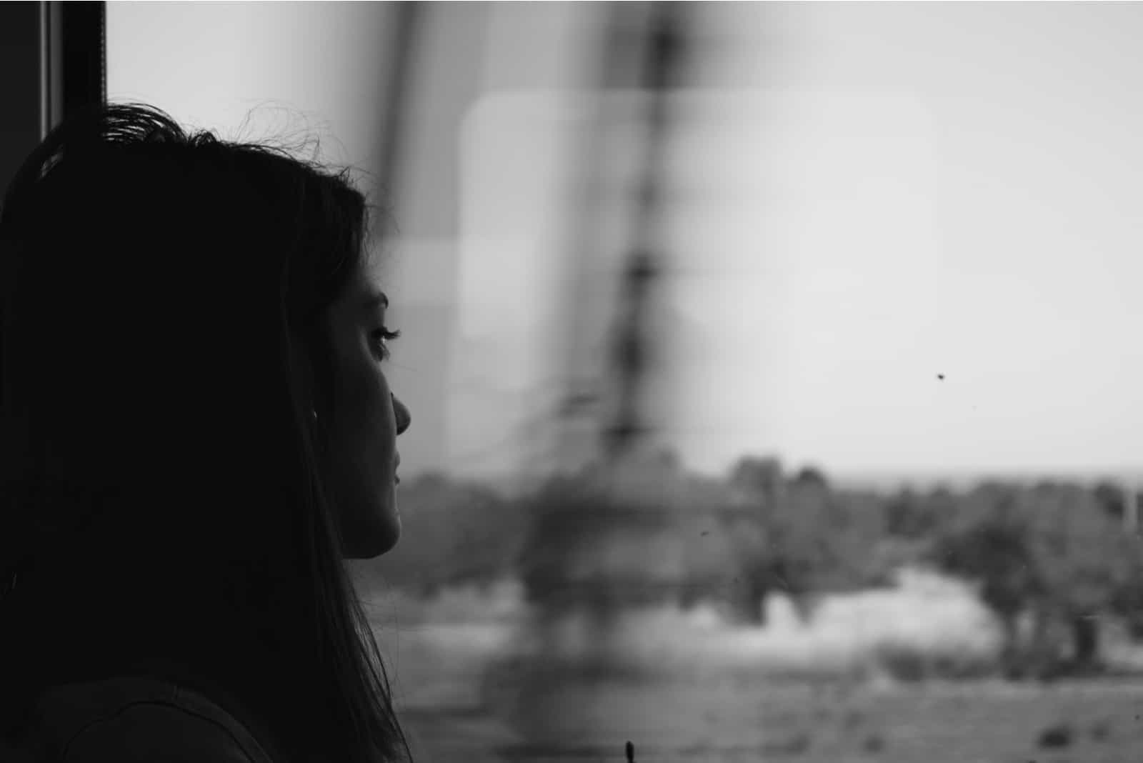 une femme triste regarde par la fenêtre