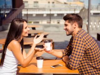 un homme et une femme sont assis à une table à l'extérieur et parlent autour d'un café
