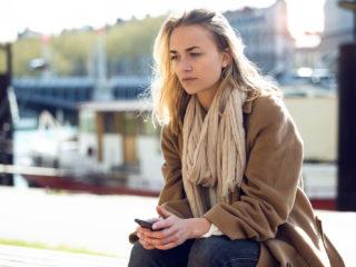 une femme imaginaire aux cheveux blonds est assise et tient un téléphone à la main