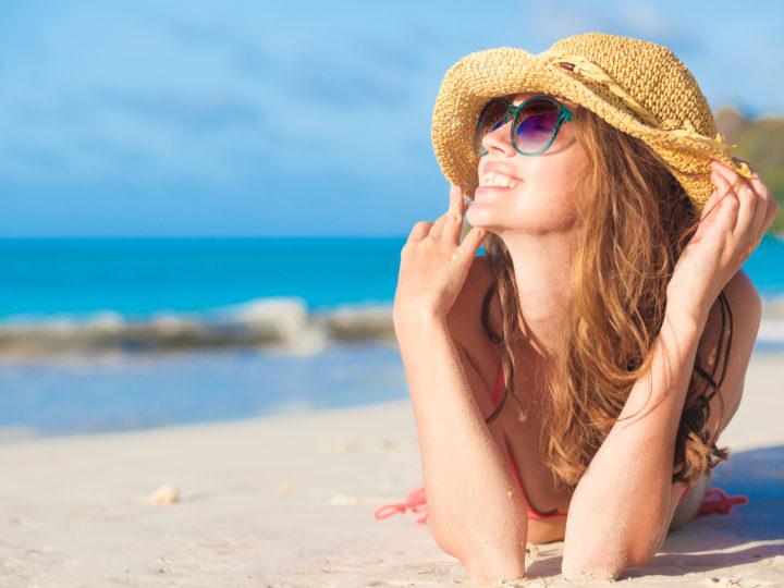 une femme souriante avec un chapeau sur la tête se trouve sur la plage