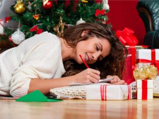 une belle femme est assise à une table et écrit une carte de voeux