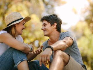 un couple d'amoureux souriant assis sur l'herbe et parlant