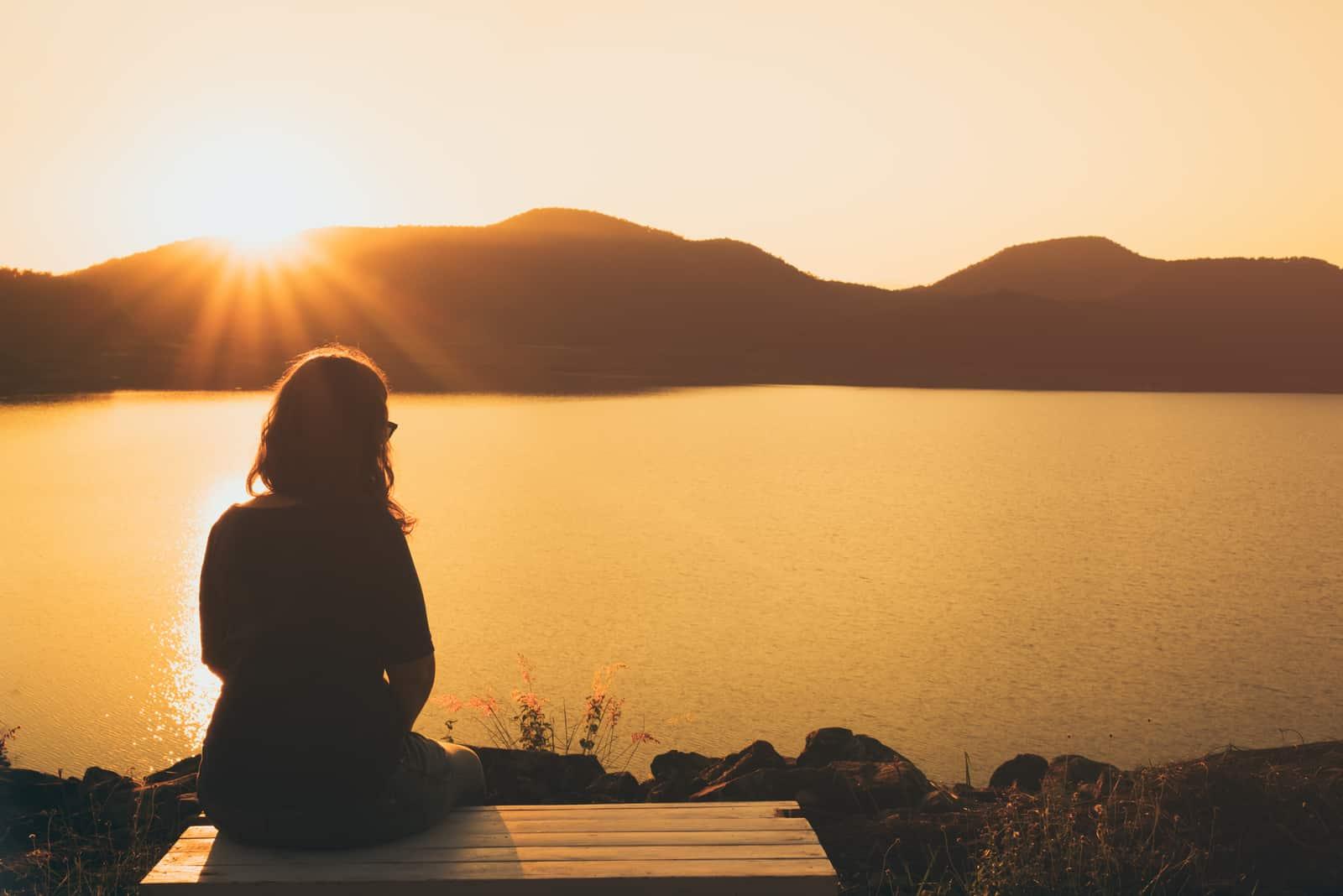 la femme est assise sur un banc et regarde le lac