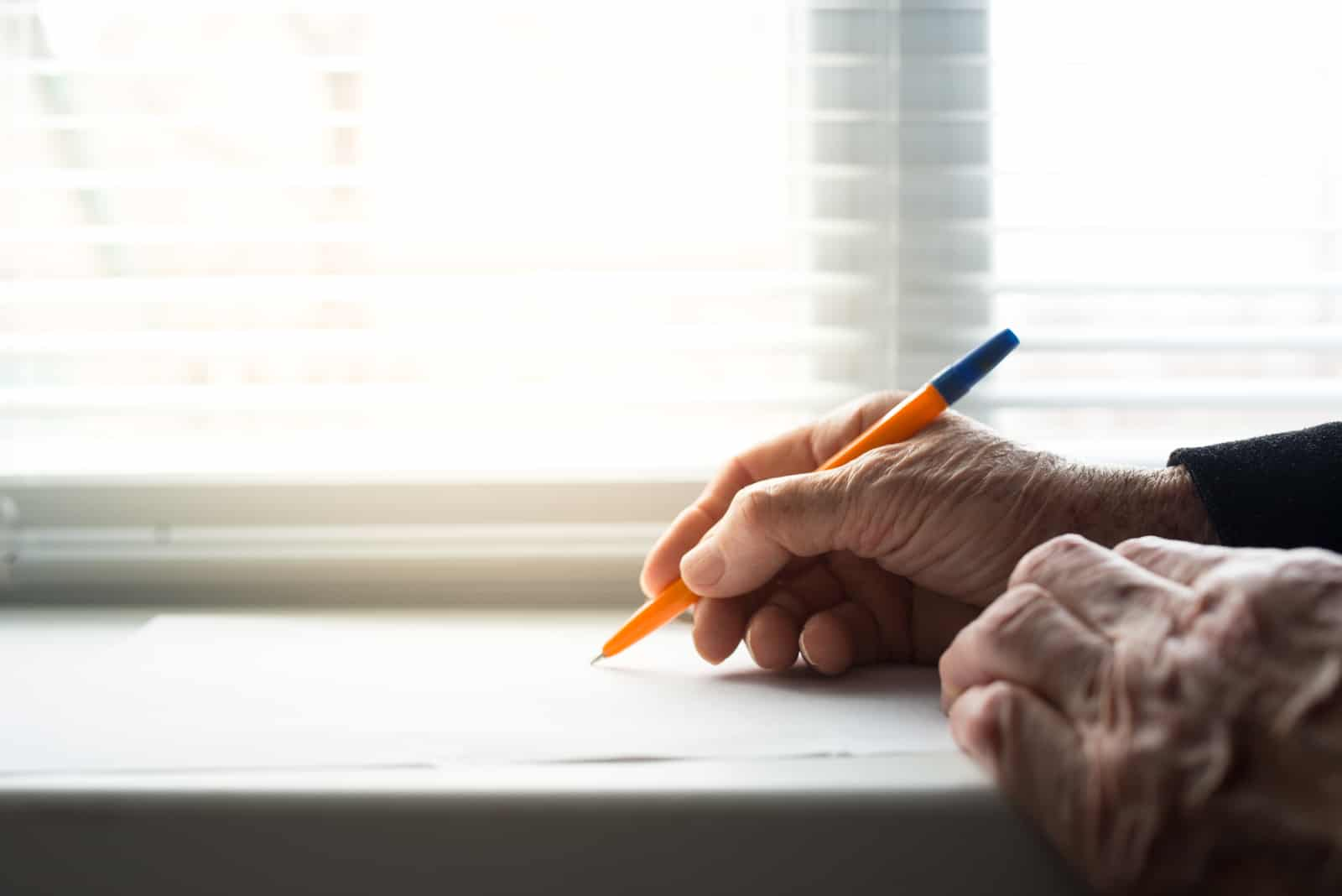 un homme est assis à une table et écrit