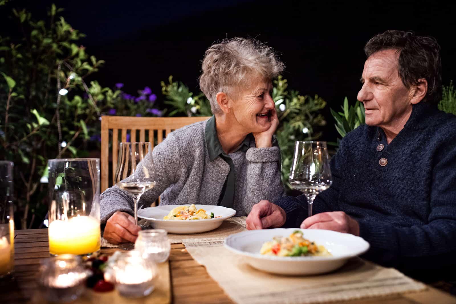 un homme et une femme à table boivent du vin