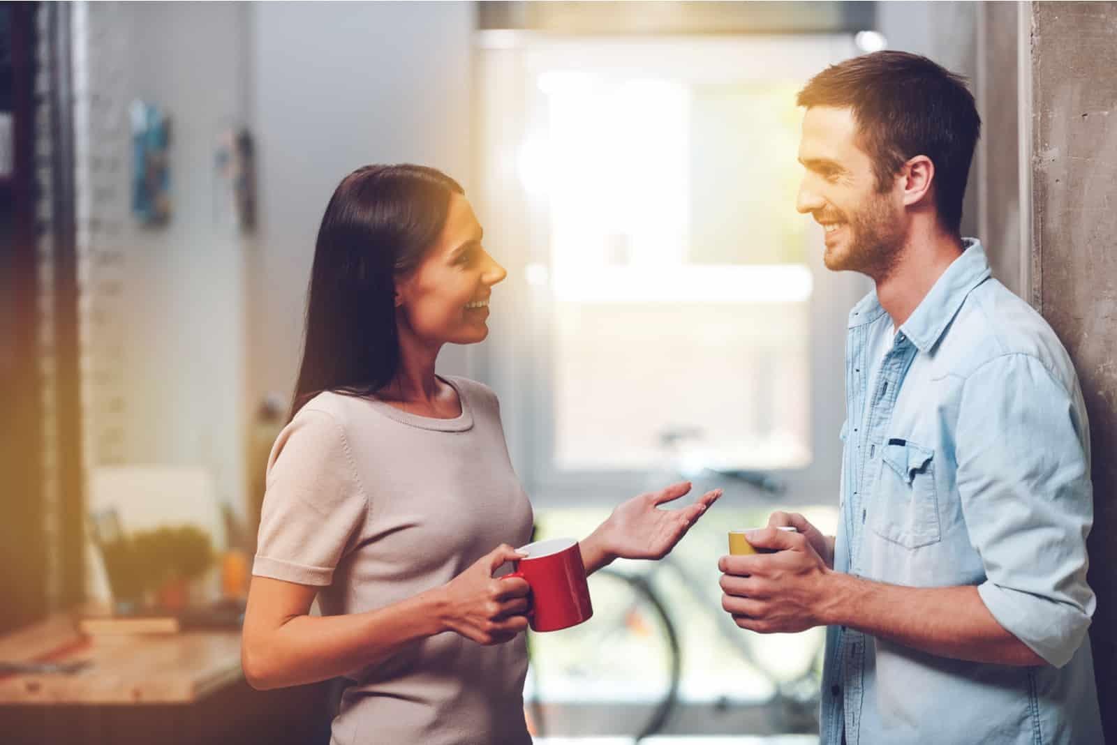 un homme et une femme debout tenant des tasses dans leurs mains et parlant