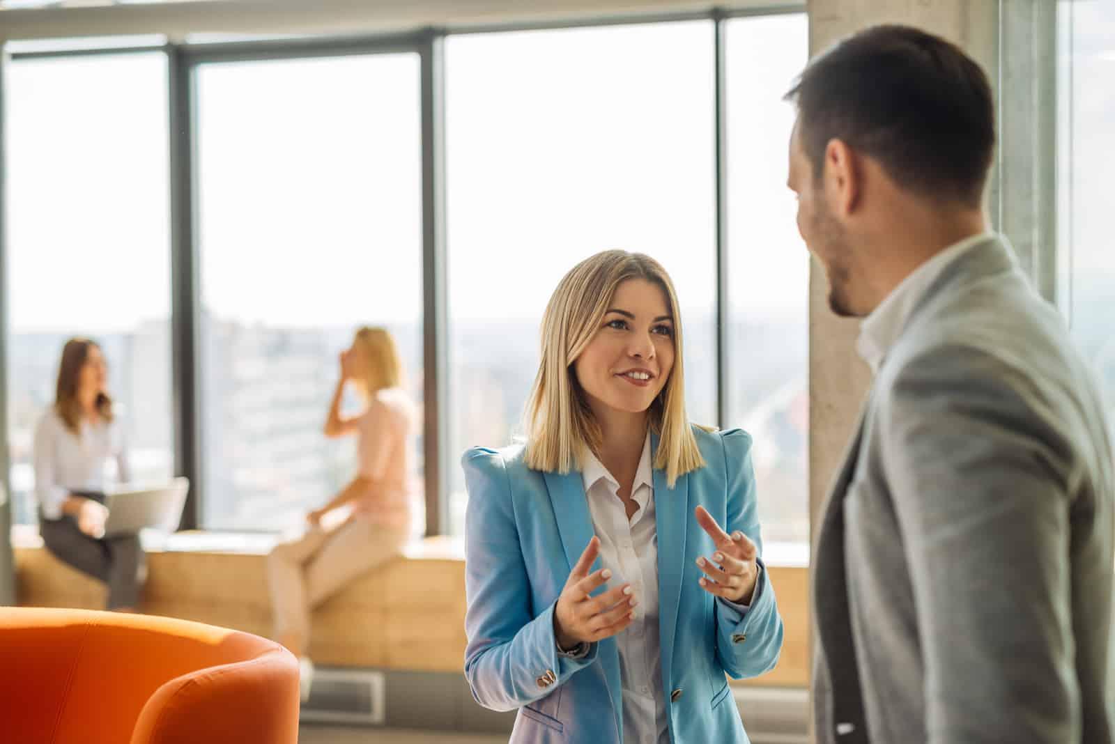 un homme et une femme discutent au bureau