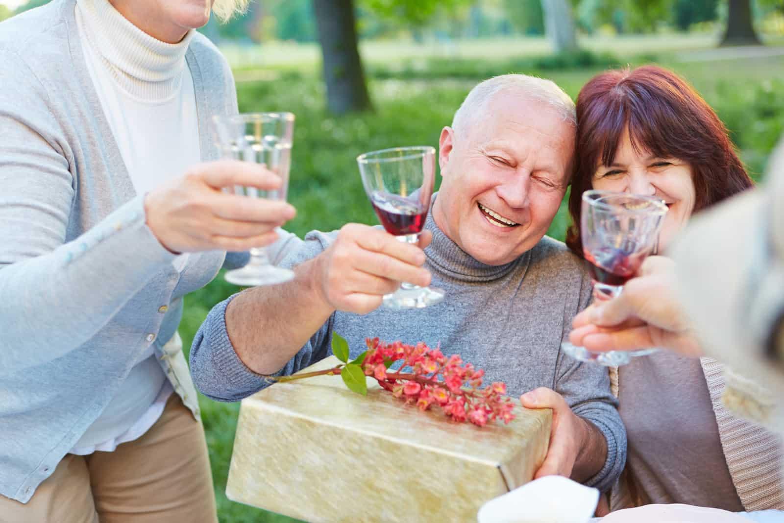 un homme et une femme tiennent un cadeau à la main et trinquent avec du vin