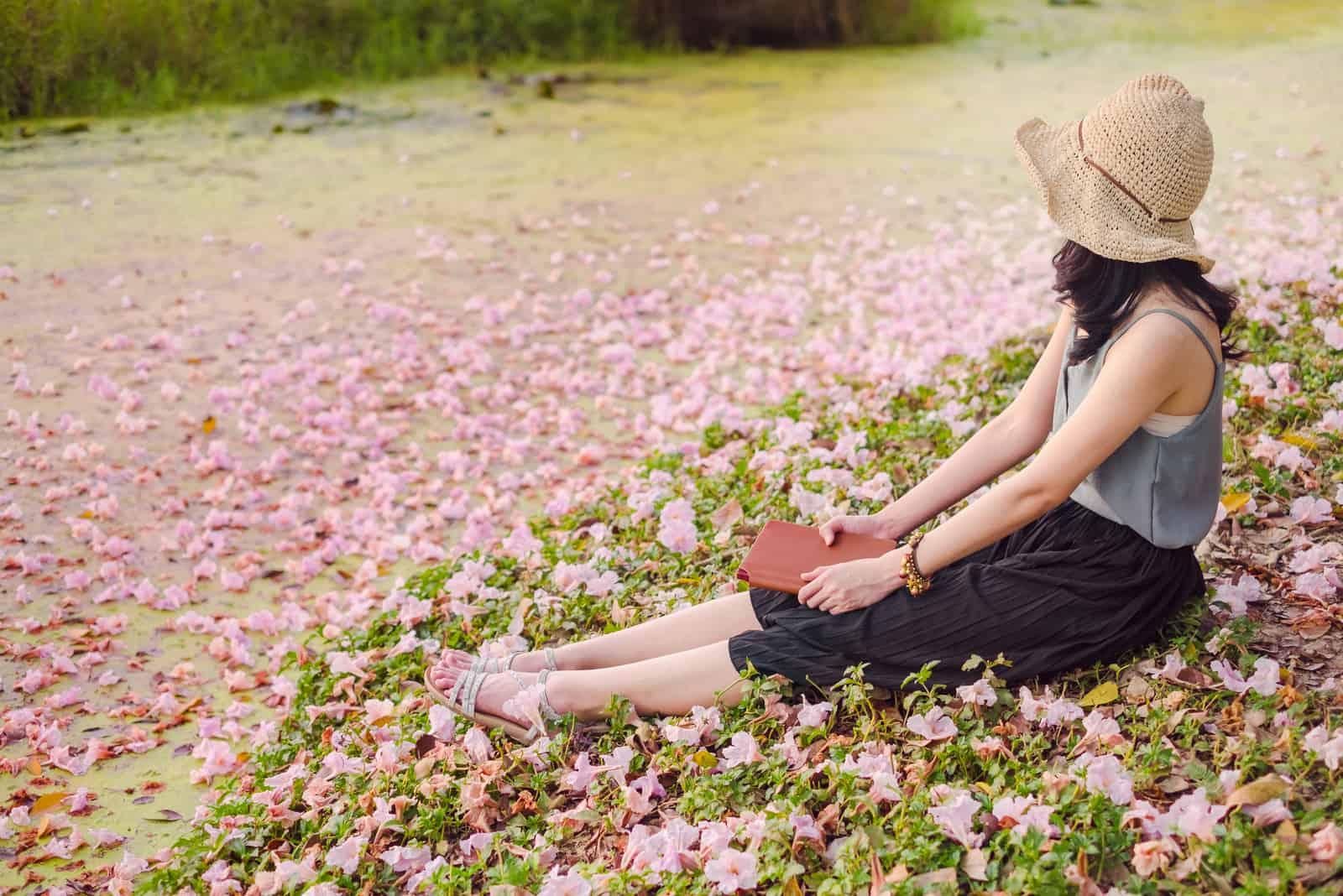 une femme avec un chapeau sur la tête est assise dans l'herbe