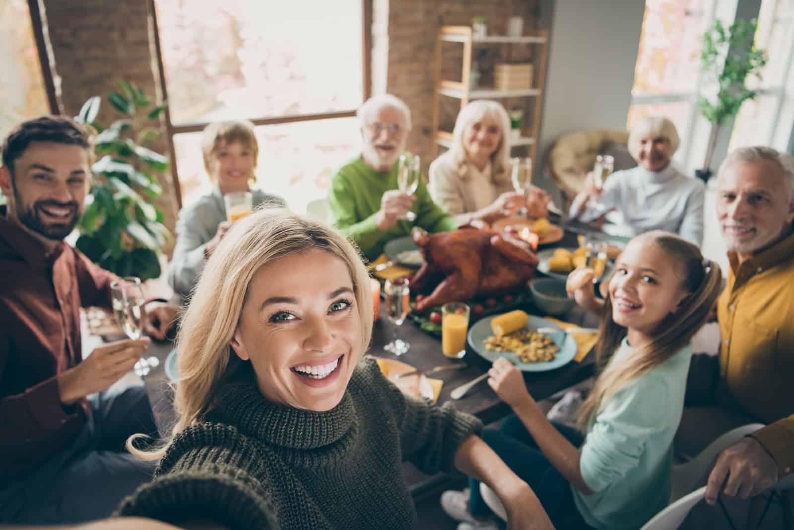 une femme blonde souriante peint une famille à table