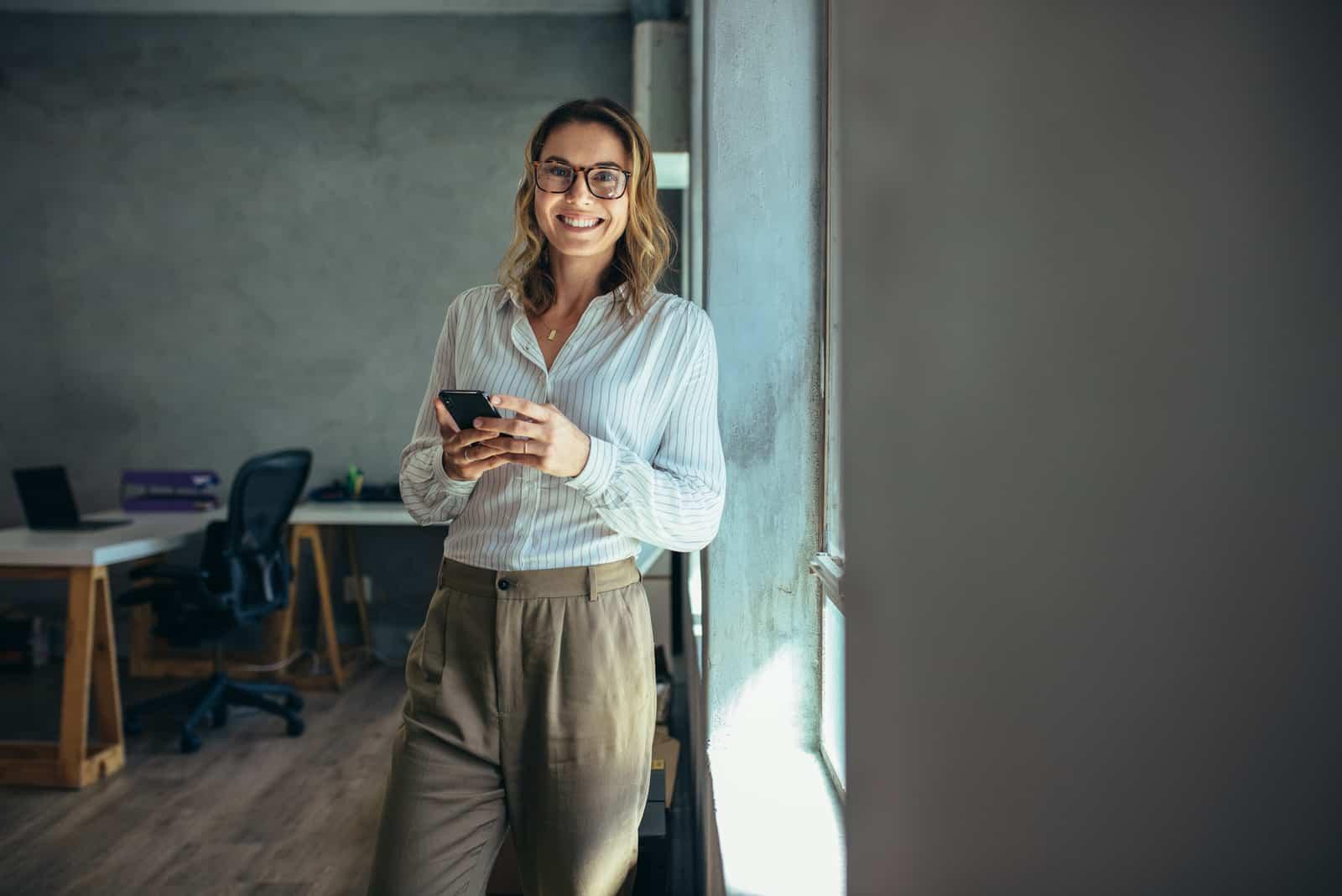 une femme souriante se tient appuyée contre un mur et tient un téléphone à la main